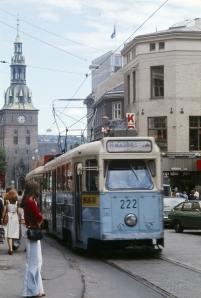 Gateløp, forretningsgårder, trikk, biler, mennesker, gateliv og Oslo Domkirke