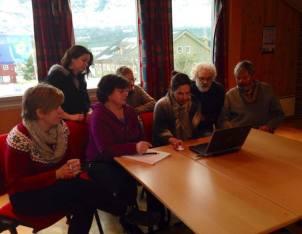En gjeng med kursdeltakere samles omkring en PC
