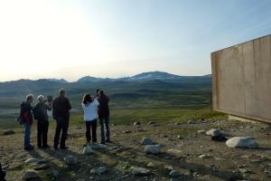En gruppe mennesker står ved Viewpoint Snøhetta og ser utover fjellheimen i stråelende solskinn. De holder opp en mobiltelefon og lærer om landskapet rundt seg