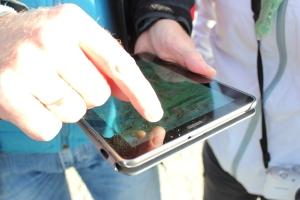 Nærbilde av et nettbrett med kart og en hånd som trykker